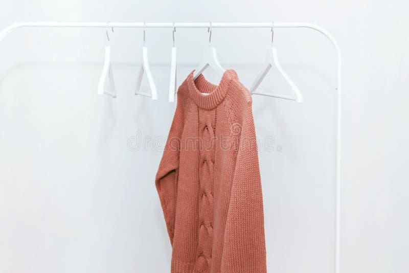 Un suéter caliente del punto en colores pastel anaranjado en la suspensión y muchas suspensiones vacías fotos de archivo