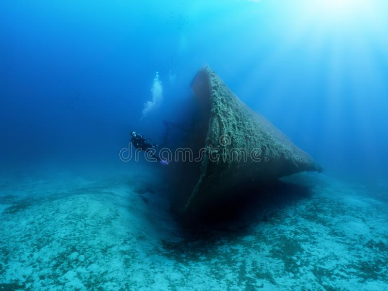 Un subaqueo esplora un naufragio incavato nel mar Mediterraneo fotografie stock