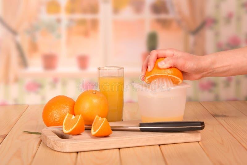 Un succo d'arancia di vetro, arance e pezzi di tenuta femminile della mano fotografia stock libera da diritti