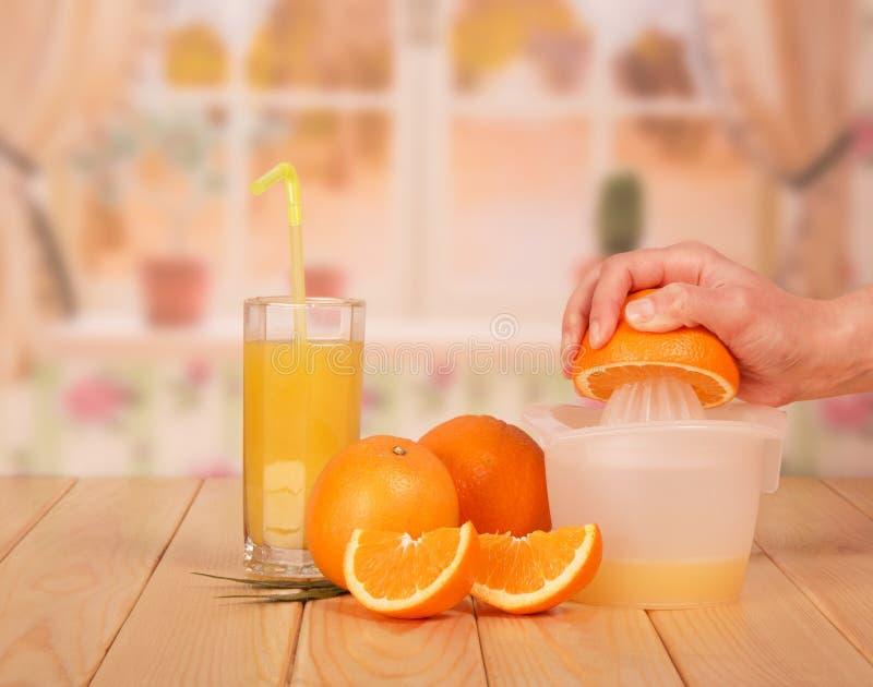 Un succo d'arancia di vetro, fette arancio, tenuta mezza o della mano del ` s della donna fotografia stock