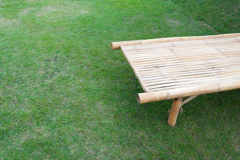 Un suelo de bambú de la silla en del césped el fondo trasero naturalmente imagenes de archivo