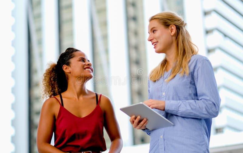 Un support de fille de métis et discuter avec la fille caucasienne blanche qui tient le comprimé photos stock