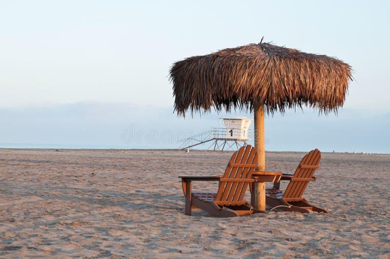 Un support de parapluie de paume au-dessus des chaises en bois d'adirondack sur une plage de l'océan pacifique photo stock