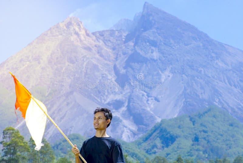 Un supporto dell'uomo con i supporti della bandiera dell'Indonesia con il fondo di Merapi Mt concetto di celebrazione di festa de fotografia stock libera da diritti