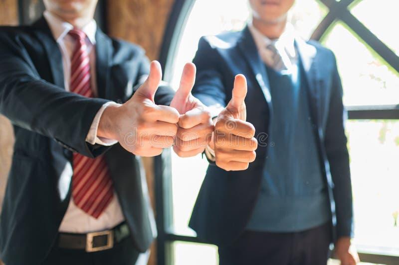 Un supporto e una manifestazione di due uomini d'affari sfogliano sulla loro mano a dimostrare il loro accordo firmare l'accordo  fotografia stock libera da diritti