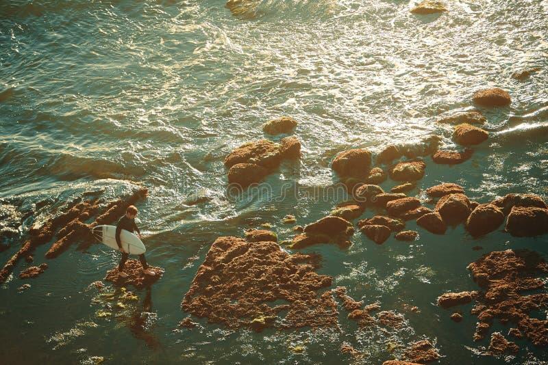 Un surfer masculin avec la planche de surf sur un récif coralien d'une mer image stock