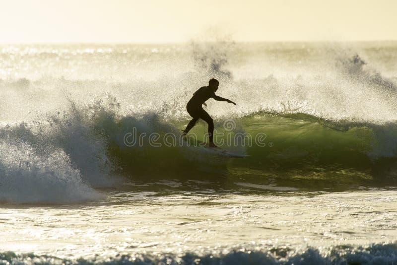 Un surfer surfant à la plage de baie du ` s de Betty au coucher du soleil dans le Cap-Occidental, Afrique du Sud photos stock