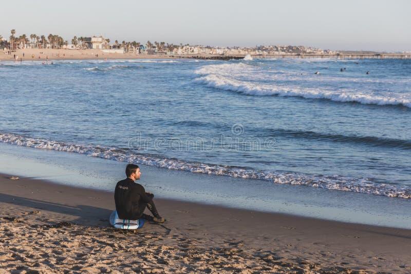 Un surfista che si siede sulla spiaggia in Venice Beach fotografia stock