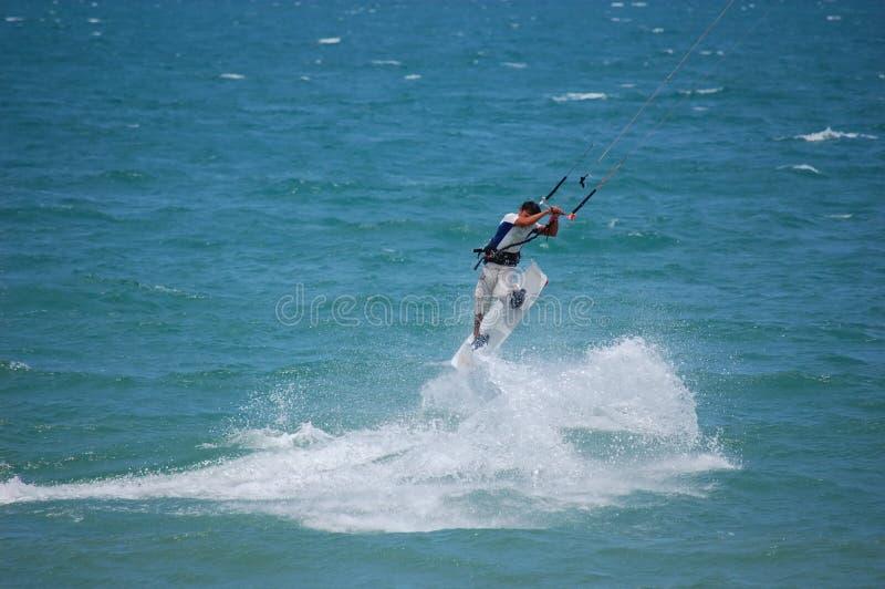 Un surfista dell'aquilone guida le onde fotografia stock libera da diritti