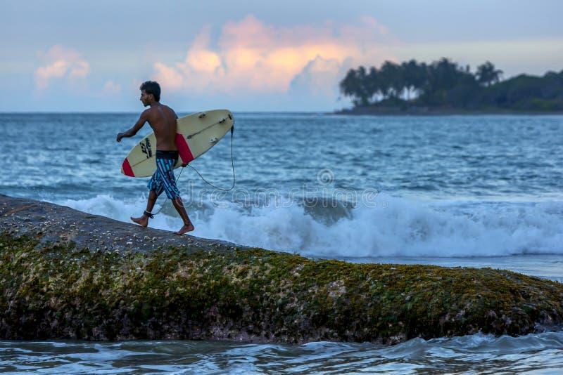 Un surfista prepara saltare giù una roccia di otto stelle per praticare il surfing una rottura della spiaggia verso la fine del p immagini stock libere da diritti