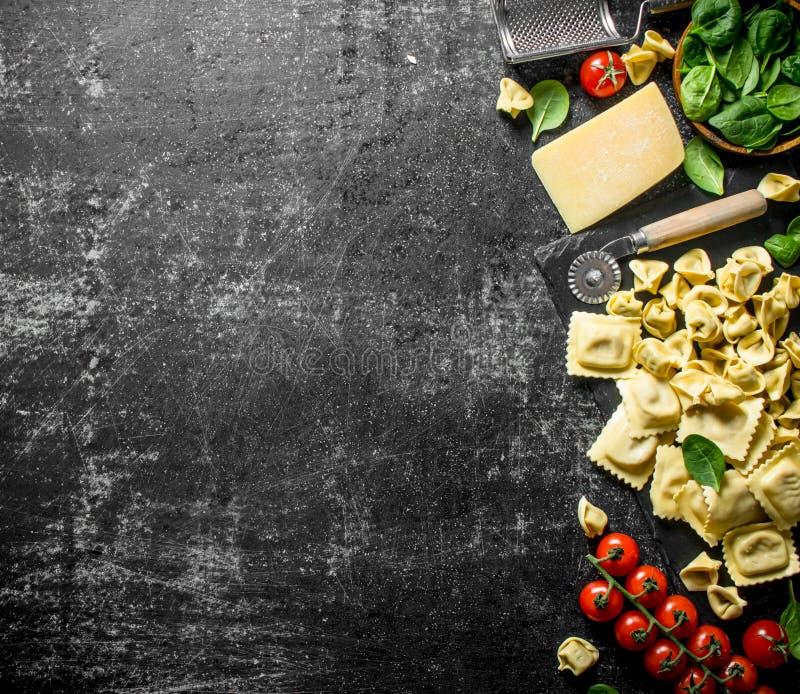 Un surtido de diversos tipos de pastas crudas con queso, tomates e hierbas imagen de archivo libre de regalías