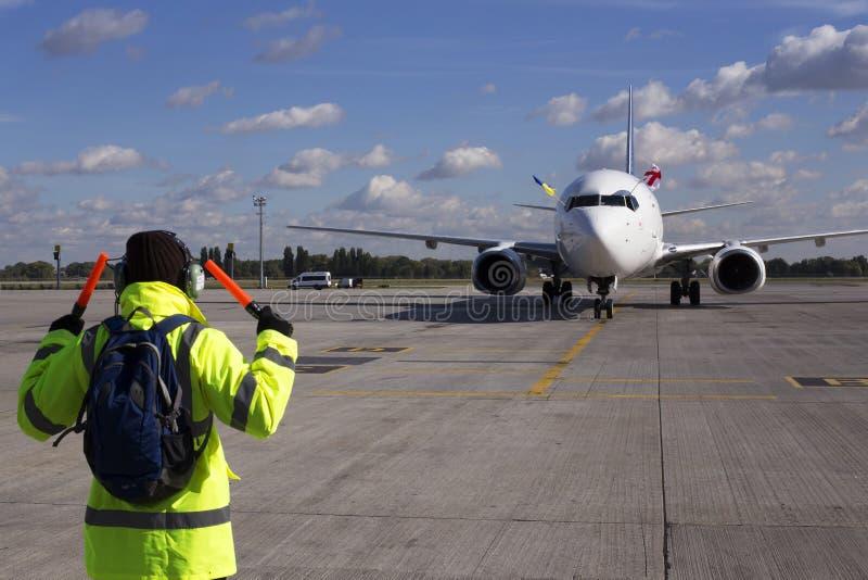 Un surveillant aide au stationnement d'avions photos stock