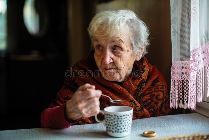 Un tè bevente di signora anziana che si siede ad una tavola nella casa aiuto immagini stock
