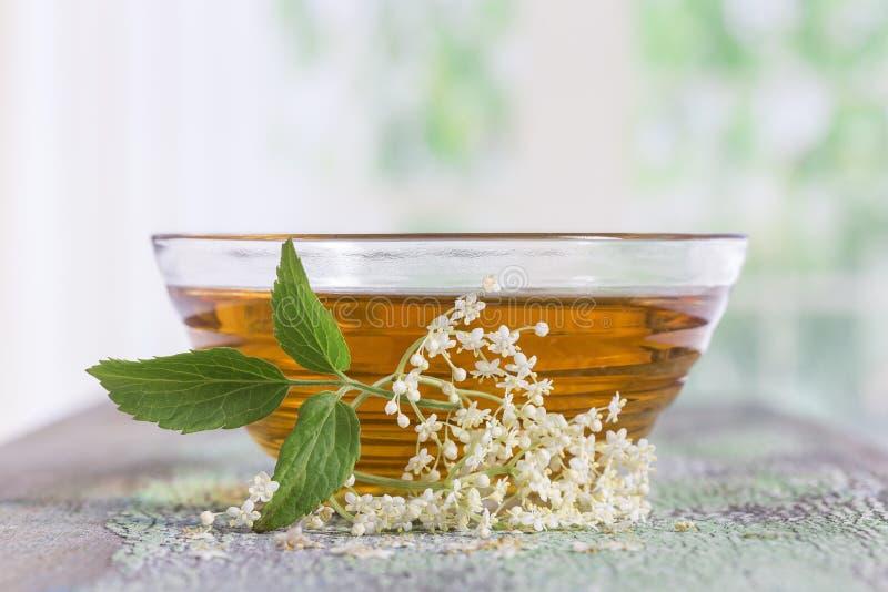 Un té del elderflower del bowlof con una puntilla de flores frescas y de hojas foto de archivo libre de regalías