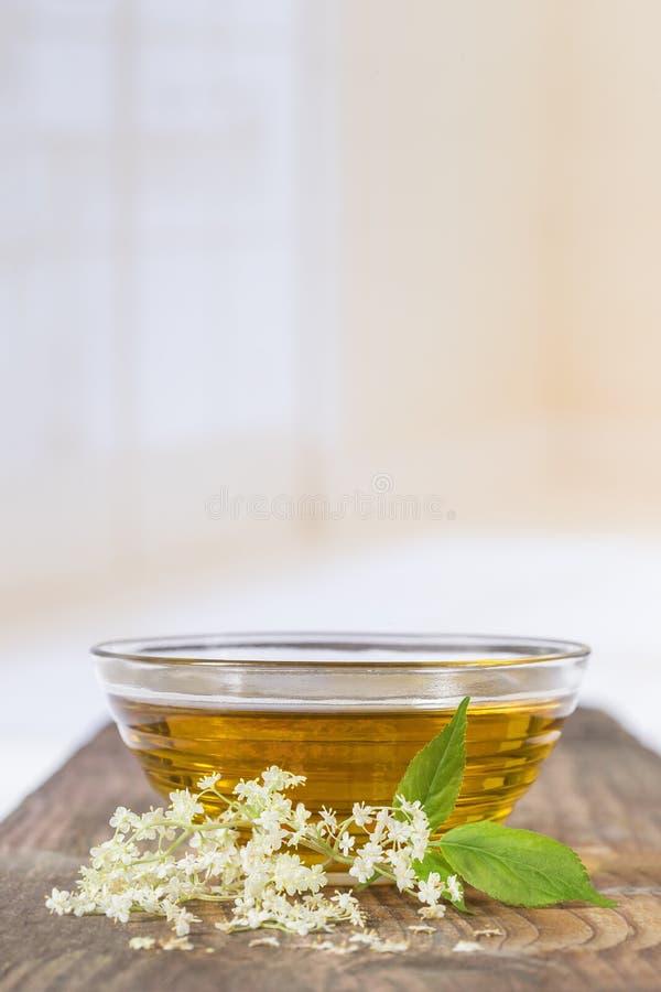 Un té del elderflower del bowlof con una puntilla de flores frescas y de hojas fotografía de archivo