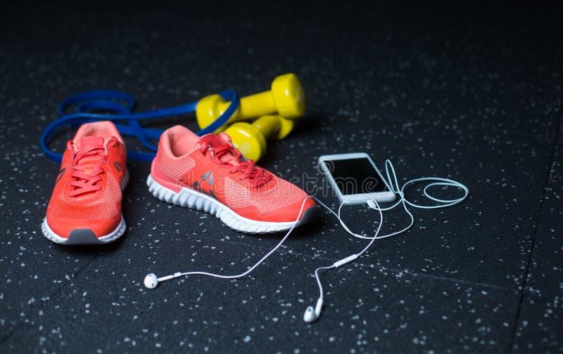 Un téléphone portable blanc avec des écouteurs, des espadrilles roses, deux haltères jaunes et extenseur sur un fond brouillé photos libres de droits