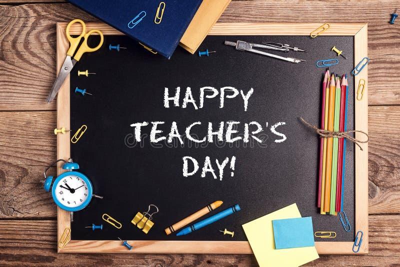 Un tableau avec le jour heureux de professeurs des textes écrit dans lui, les fournitures scolaires et le réveil sur une table en photos stock