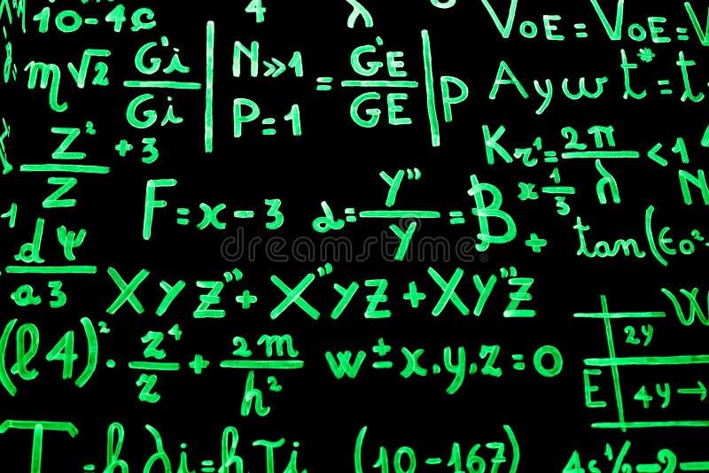 Un tableau noir complètement des équations mathématiques écrites avec la peinture phosphorescente pour faciliter étude images libres de droits