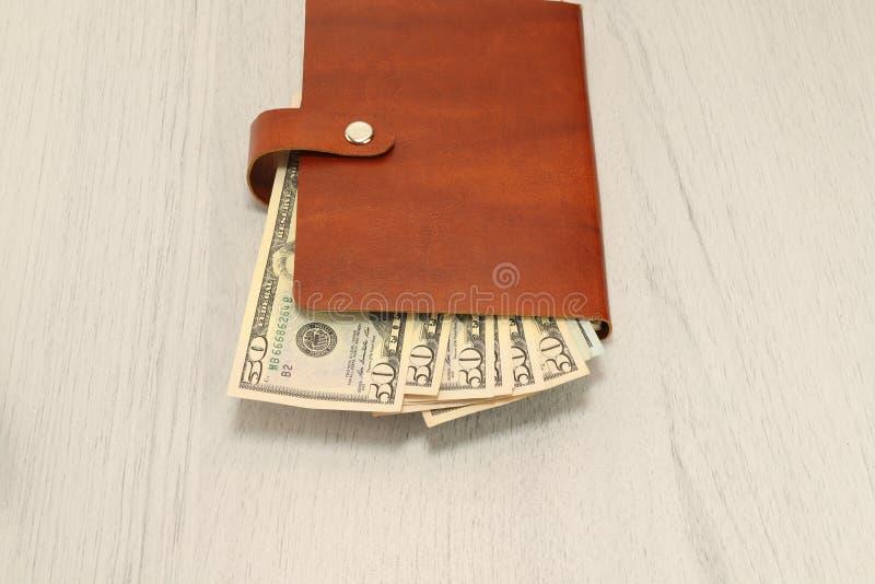 Un taccuino marrone di cuoio con i dollari dei contanti si trova su una scrivania Composizione orizzontale, fondo fotografia stock libera da diritti