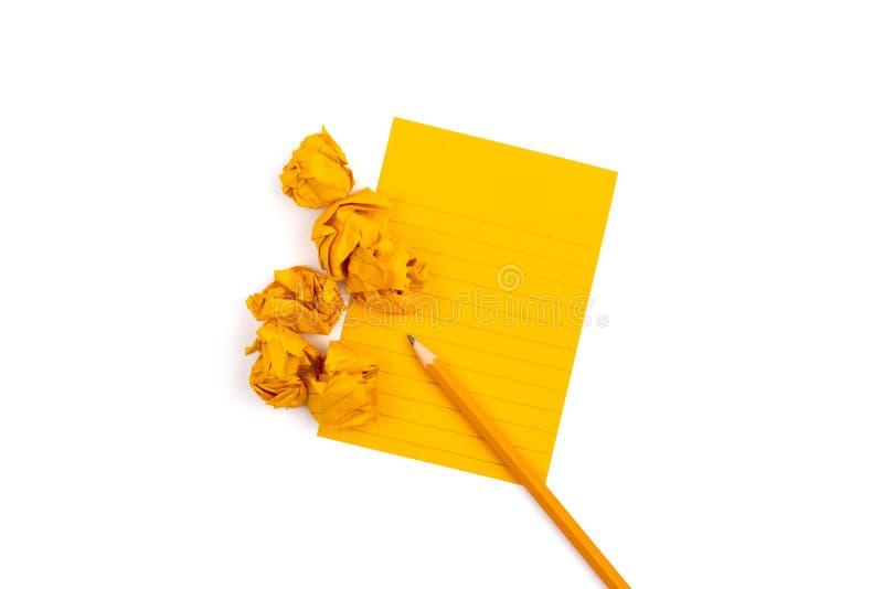 Un taccuino a strisce con gli strati arancio accanto a cui si trova una matita affilata e sei pezzi di carta sgualciti su fondo b fotografia stock libera da diritti