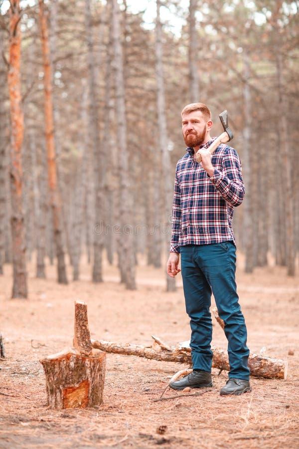 Un taglialegna, supporti con un'ascia in sua mano accanto al legno all'aperto fotografia stock