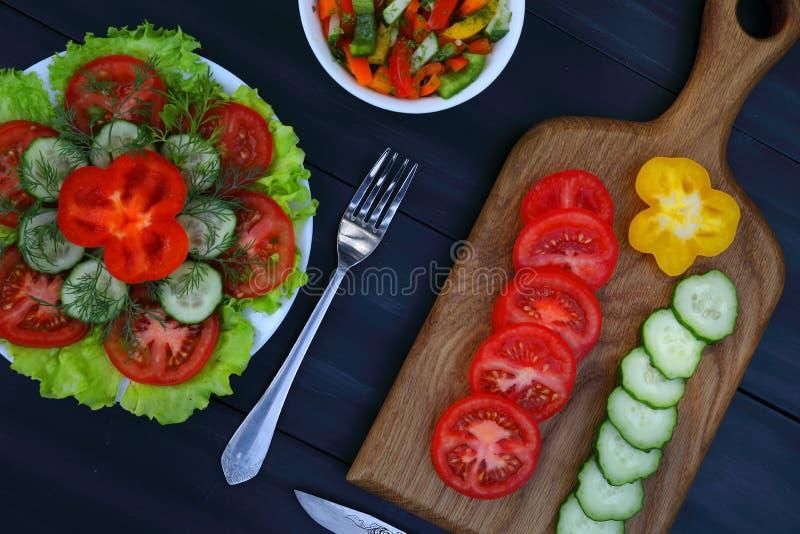 Un tagliere con le verdure e le insalate su un fondo scuro fotografia stock libera da diritti