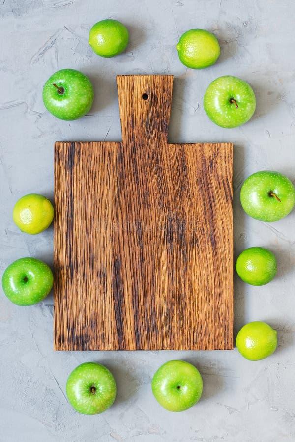 Un tagliere di legno vuoto su un fondo concreto grigio è circondato dalle mele e dalla calce verdi immagini stock libere da diritti