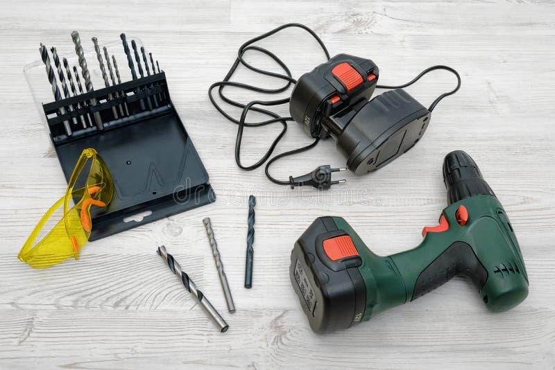 Un taladro sin cuerda, una batería de repuesto, un sistema de pedazos y gafas de seguridad amarillas en fondo de madera de la tab imagen de archivo libre de regalías