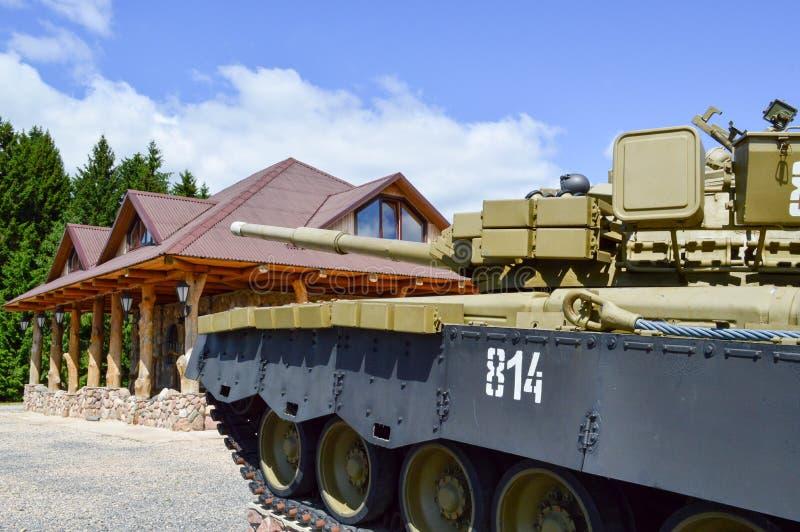 Un tanque de batalla militar verde grande del metal del hierro con un cañón se monta parqueó al lado de la casa de la cabaña con  fotos de archivo