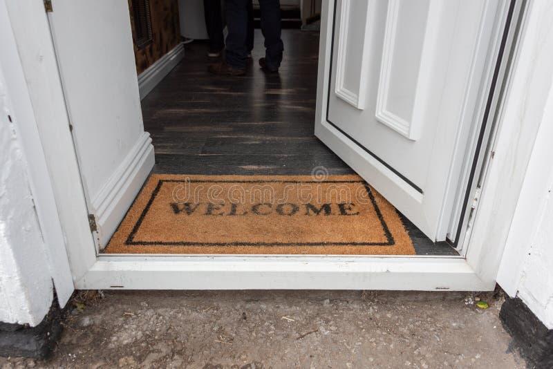 Un tapis bienvenu rétro-dénommé de plancher placé dans une entrée de porte photo stock