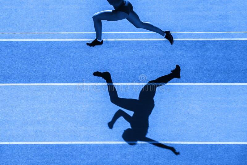 Un taqueur caucasien de coureur de femme fonctionnant en silhouette sur le fond de stade Filtre de couleur bleu photo libre de droits