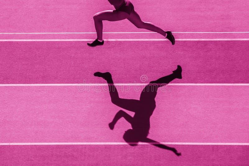 Un taqueur caucasien de coureur de femme fonctionnant en silhouette sur le fond de stade Filtre de couleur rose photographie stock libre de droits
