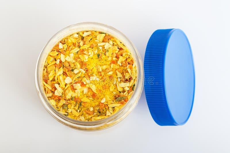 Un tarro abierto con el condimento universal en un cierre blanco del fondo para arriba El condimento contiene la sal y los pedazo imágenes de archivo libres de regalías