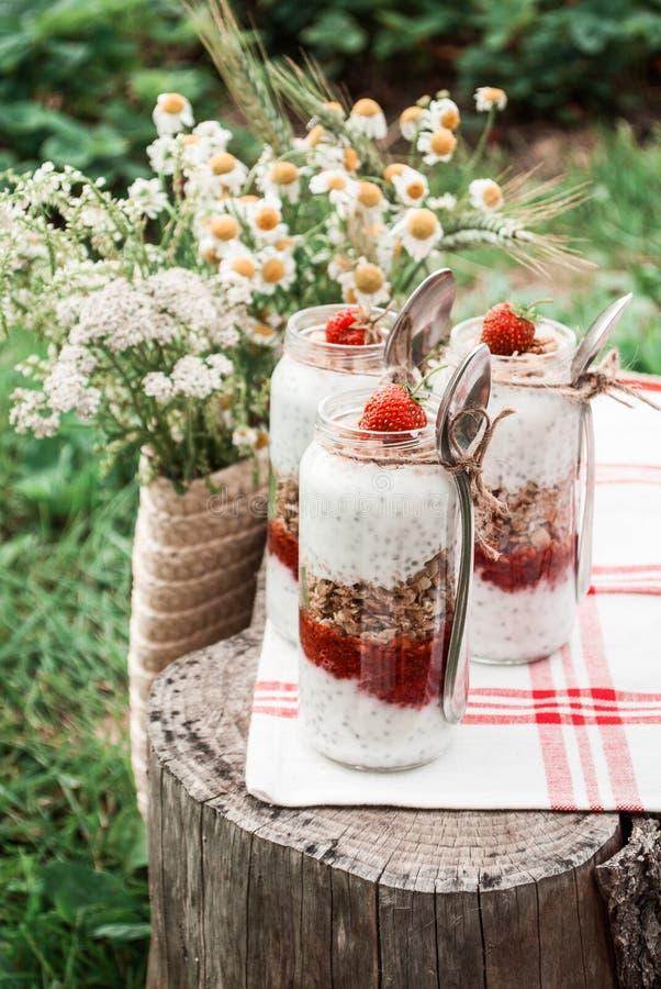 Un tarro de cristal con un postre de fresas, del yogur con Chia y del granola en una comida campestre en un estilo rústico foto de archivo libre de regalías