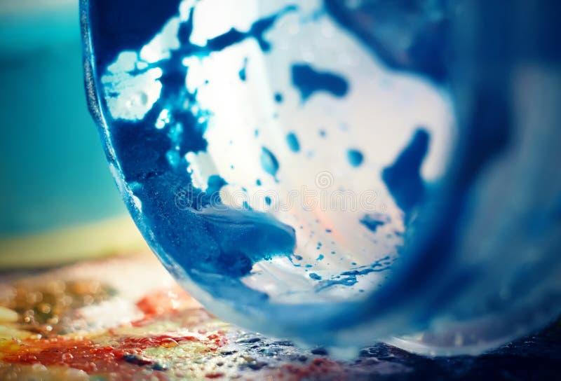 Un tarro de pintura azul brillante del aguazo cayó en una paleta multicolora foto de archivo