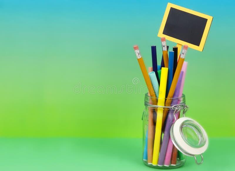 Un tarro hermético claro llenado de los marcadores y de los lápices coloreados en un fondo verde azul graduado fotos de archivo