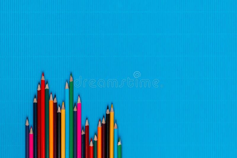 Un tas de crayons sur fond bleu, tiré d'en haut, aligné en bas à gauche, fermé photo libre de droits