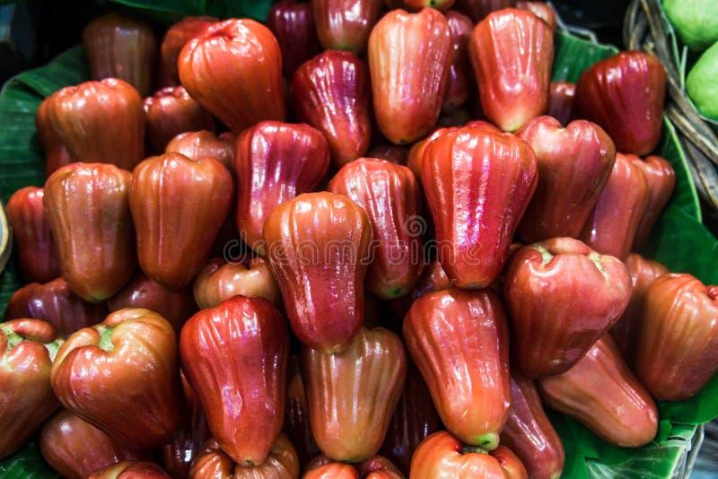 Un tas de fruit frais de pomme rose sur la feuille de banane à vendre au marché photographie stock