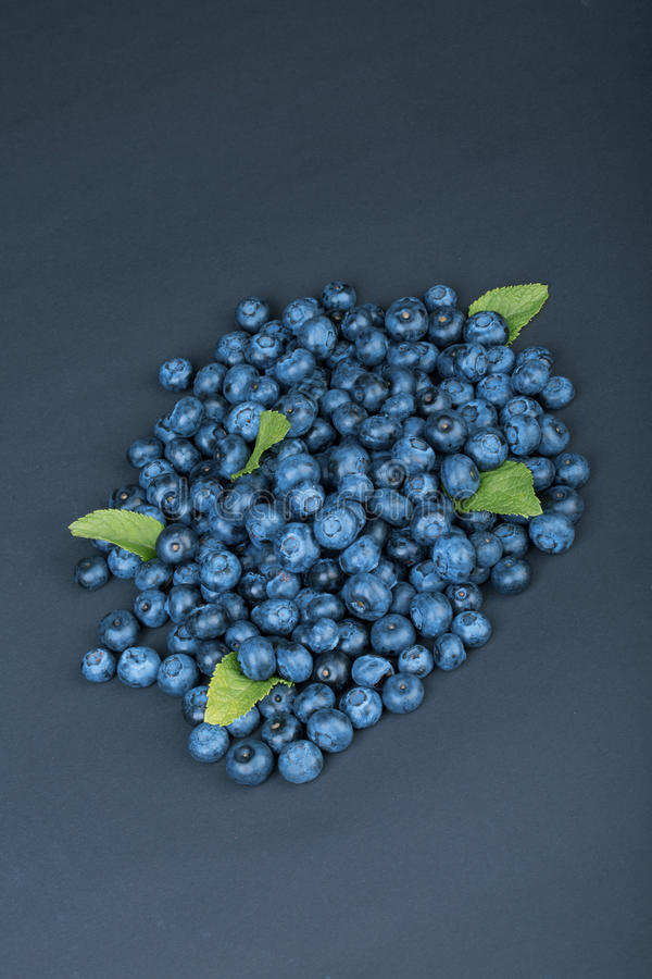 Un tas des myrtilles douces et naturelles avec la menthe sur un fond bleu-foncé Ingrédients organiques pour les casse-croûte sain photographie stock libre de droits