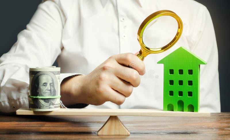 Un tasador de las propiedades inmobiliarias estima el coste de vivienda Precio justo para la venta de un apartamento o de una cas foto de archivo