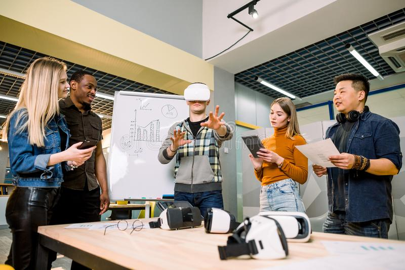 Un team di imprenditori multietnici che presenta la realtà virtuale in un incontro di lavoro per il giovane e bello capo dell'uom fotografia stock libera da diritti