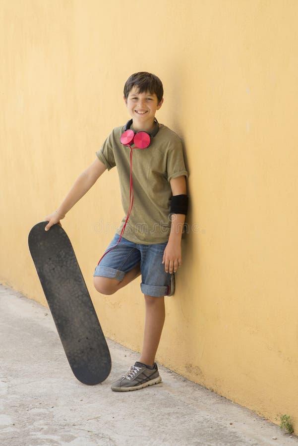 Un teenager con il pattino sulla via della città fotografia stock