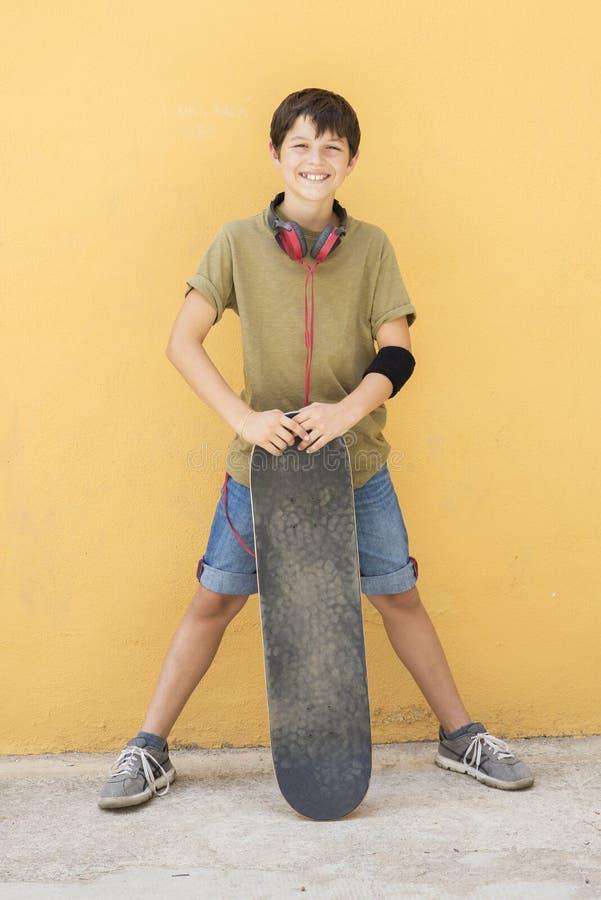 Un teenager con il pattino sulla via della città fotografie stock libere da diritti