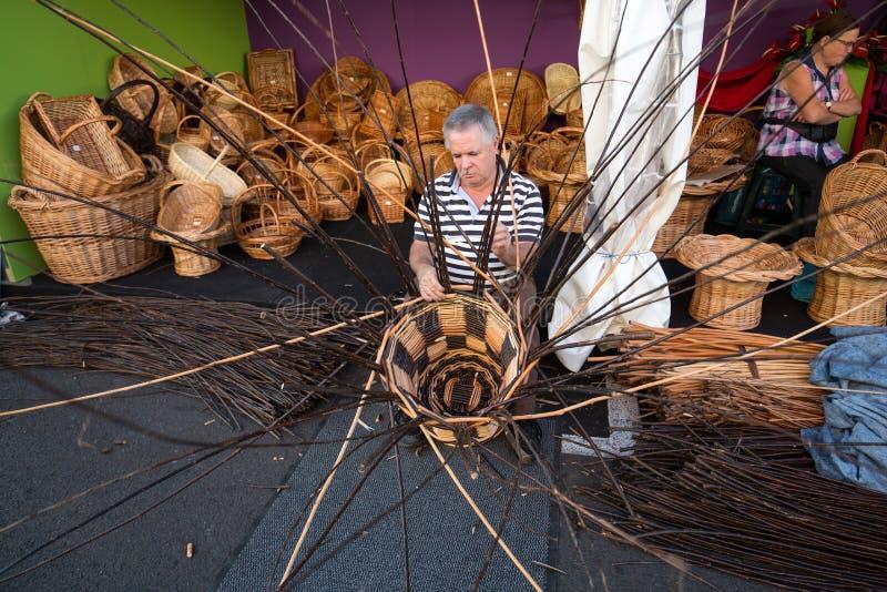 Un tejedor de la cesta en el trabajo en la tienda de la fábrica en Camacha Madeira fotografía de archivo