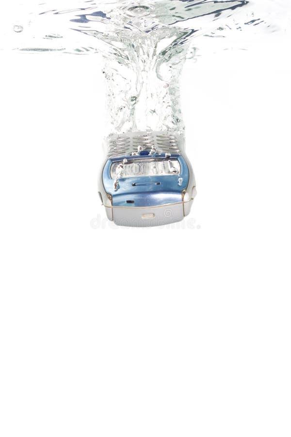 Un teléfono celular que cae en el agua imagen de archivo