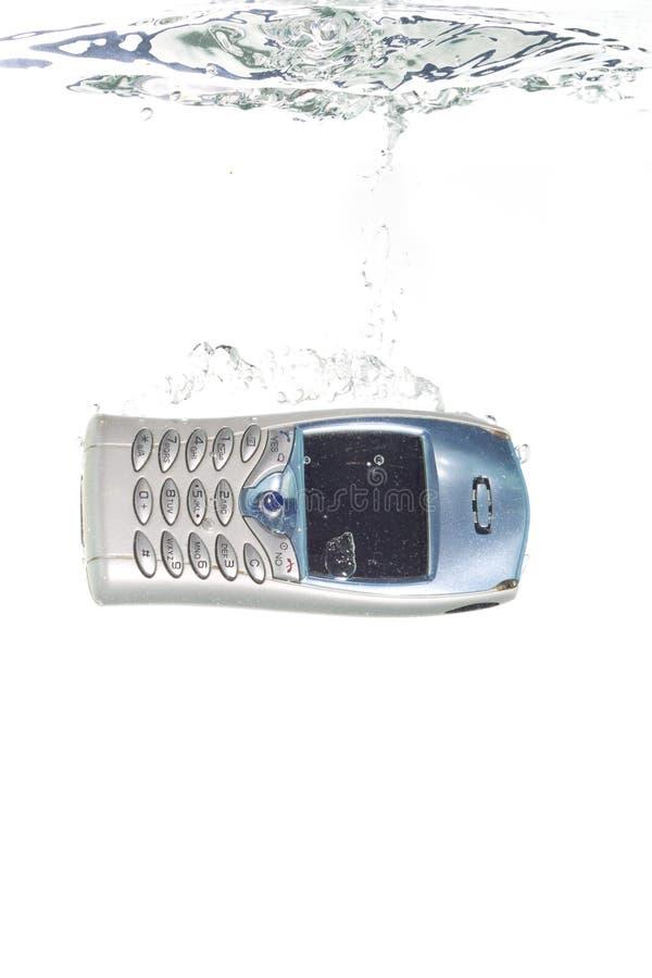 Un teléfono celular que cae en el agua fotografía de archivo