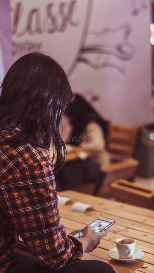 Un teléfono de la tenencia de la muchacha mientras que goza de una taza de macchiato del café express en cafetería imagen de archivo