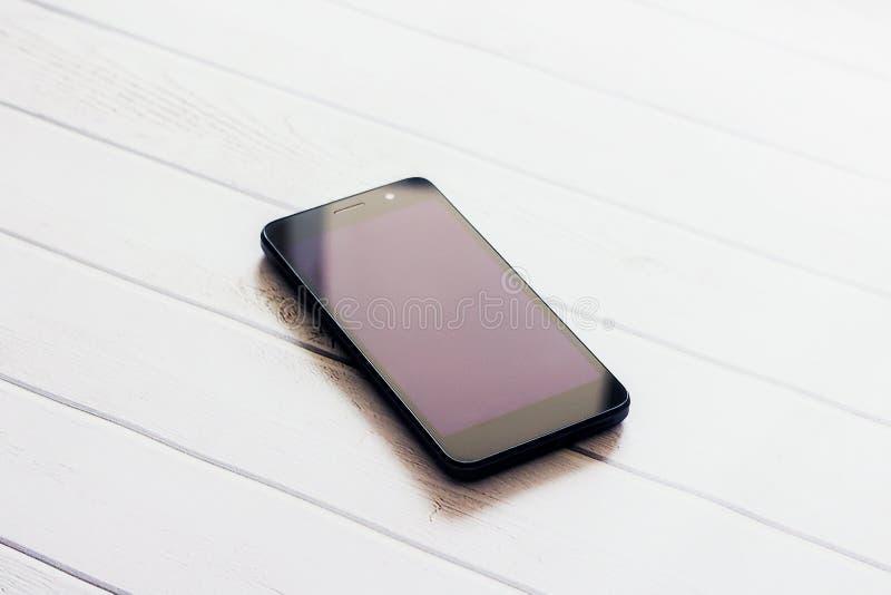 Un teléfono elegante con la pantalla en el fondo de madera foto de archivo