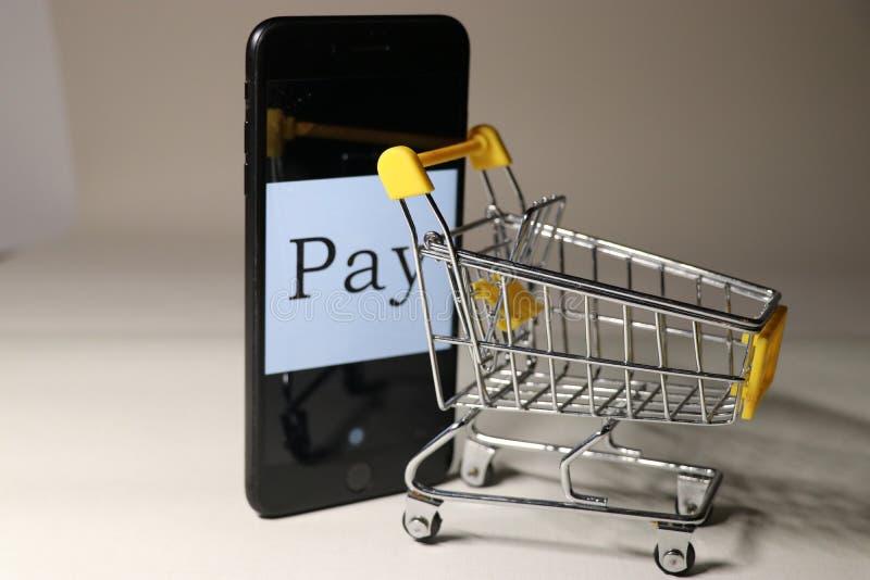 Un teléfono móvil está empujando un carro de la compra imágenes de archivo libres de regalías
