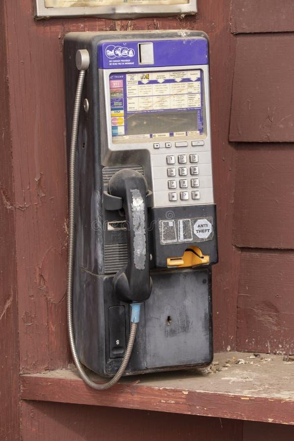 Un teléfono público en un fondo de madera fotos de archivo libres de regalías